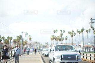 車の横に通りを歩く人々 のグループの写真・画像素材[813735]