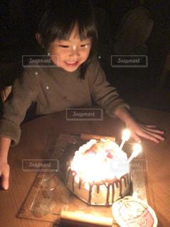 キャンドルとバースデー ケーキでテーブルに座っている人の写真・画像素材[1667518]