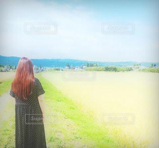 草の覆われてフィールド上に立っている人の写真・画像素材[1599387]