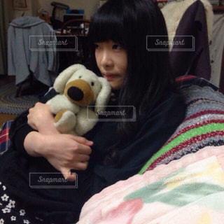 ベッドの上の動物のぬいぐるみを持っている人の写真・画像素材[1633933]