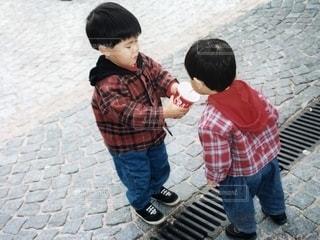 歩道で弟に飲み物を与える兄の写真・画像素材[2202628]