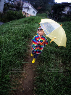 子ども,雨,傘,カラフル,歩く,散歩,黄色,男子,小道,子供,草,家,外,土,長靴,こども,幼児,雨天,イエロー,初夏,梅雨,少年,男の子,天気,レインコート,虹色,雨の日,草むら,カッパ,幼稚園児,合羽,男児,雨空,レインボーカラー