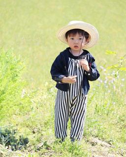 草の上に立っている小さな男の子の写真・画像素材[2095593]