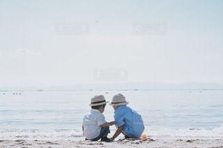ビーチに座っている男の写真・画像素材[3552268]
