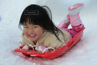 雪の中で座っている女の子の写真・画像素材[1717494]