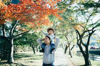 木の隣に立っている少年の写真・画像素材[1614274]