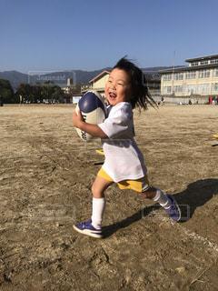 ラグビーボールを抱えてダッシュする子どもの写真・画像素材[1616824]