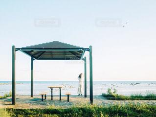 海岸をバックに佇む女性の写真・画像素材[2144829]