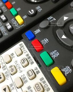 卓上のテレビとBlu-rayのリモコンの写真・画像素材[1538300]