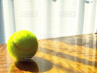 木製テーブルの上にテニスボールの写真・画像素材[1549314]
