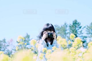 菜の花畑とカメラ女子の写真・画像素材[2273597]