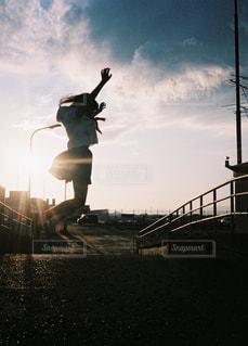 バック グラウンドで夕日を持つ人の写真・画像素材[1686415]