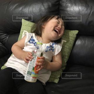 リモコンを持つソファに座っている赤ちゃんの写真・画像素材[2217330]