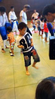 群衆の前に立つ小さな男の子の写真・画像素材[2223185]