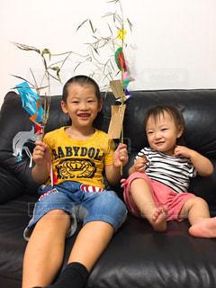 ソファに座っている小さな男の子と少女の写真・画像素材[2331438]