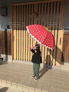 赤い傘を持っている娘の写真・画像素材[2891601]