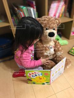 本棚の前に座っている小さな女の子の写真・画像素材[2895904]