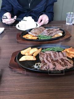 食べ物の皿を持ってテーブルに座っている人の写真・画像素材[2914907]