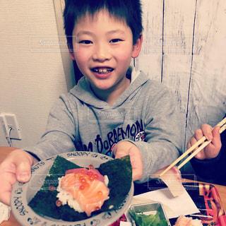 食べ物の皿を持ってテーブルに座っている若い男の子の写真・画像素材[2923047]