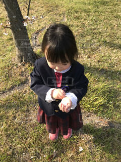 草の中に立っている小さな女の子の写真・画像素材[3140469]