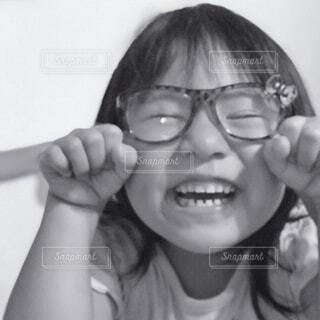 眼鏡をかけてカメラに向かって微笑む小さな女の子の写真・画像素材[3691886]