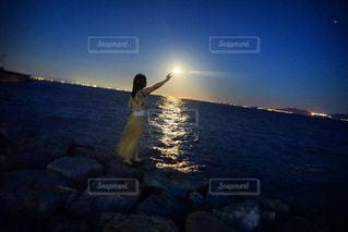 水の体の横に立っている人の写真・画像素材[1518302]