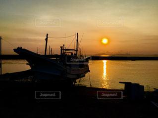 水の体のボートの後ろの夕日の写真・画像素材[2333517]