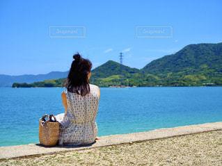 水域の前に立っている人の写真・画像素材[2379583]