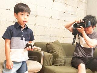 テーブルの上に座っている少年の写真・画像素材[2186868]