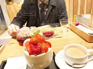 食べ物の皿を持ってテーブルに座っている人の写真・画像素材[2259743]