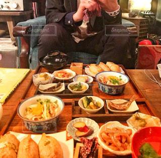 食べ物でいっぱいのテーブルに座っている人の写真・画像素材[2264027]