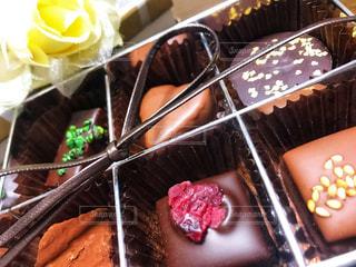 テーブルの上に座っているチョコレートケーキの写真・画像素材[2937543]