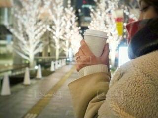 女性,冬,夜,コーヒー,綺麗,コート,マフラー,一人,女子,手持ち,イルミネーション,人物,人,セーター,紙コップ,寒い,ポートレート,見つめる,ライフスタイル,まつげ,テイクアウト,ゴールド,手元,もこもこ,片手,シャンパンゴールド