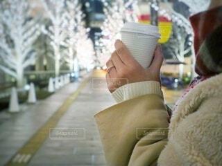 女性,冬,夜,コーヒー,綺麗,コート,一人,女子,手持ち,イルミネーション,人物,人,紙コップ,ポートレート,見つめる,ライフスタイル,テイクアウト,ゴールド,手元,もこもこ,片手,シャンパンゴールド