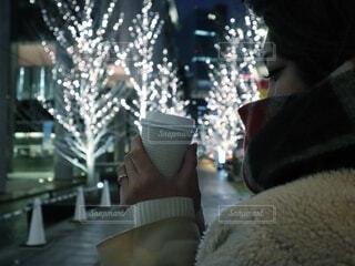 女性,冬,夜,コーヒー,綺麗,コート,マフラー,一人,女子,手持ち,イルミネーション,人物,人,美人,紙コップ,ポートレート,見つめる,ライフスタイル,まつげ,テイクアウト,ゴールド,手元,もこもこ,片手,冬物,シャンパンゴールド