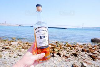 海,空,屋外,ビーチ,手,水面,岩,人物,人,ボトル,地面,ウイスキー,ドリンク,アルコール,サントリー,飲料,アンバサダー,アルコール飲料
