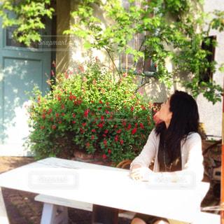 屋外テラスのテーブルに座っている人の写真・画像素材[1867919]
