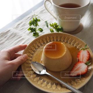 プリンのお皿を持つ手の写真・画像素材[1882439]