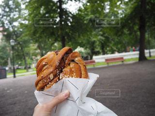 公園の中で食べるシナモンロールの写真・画像素材[2069686]