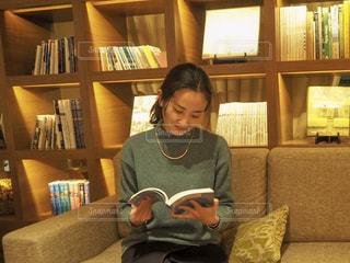 ソファーで本を読む女性の写真・画像素材[2485583]