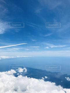 雪に覆われた山の上を飛ぶ飛行機の写真・画像素材[2432813]