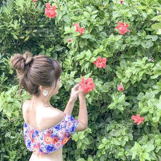 花の前に立っている人の写真・画像素材[1546399]
