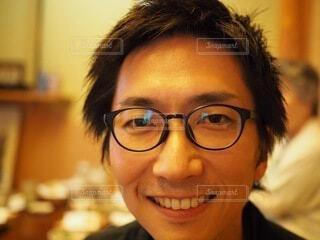 眼鏡をかけてカメラに向かって微笑む人の写真・画像素材[3656330]