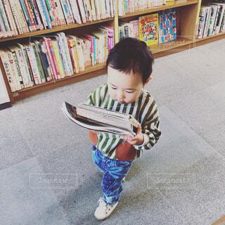 本棚を持っている小さな男の子の写真・画像素材[3694050]