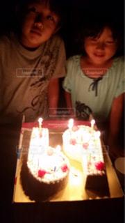 キャンドルとバースデー ケーキの前に座っている少女の写真・画像素材[1669081]