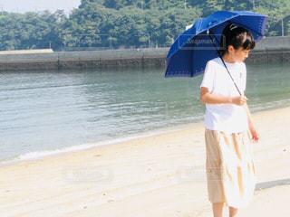 浜辺で傘をさす女の子の写真・画像素材[2234626]