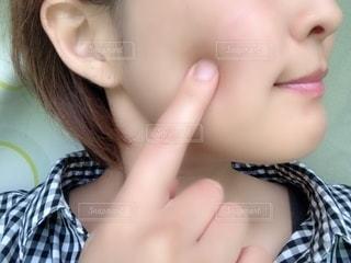 ほっぺをさわる女性の写真・画像素材[2300366]
