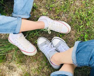 草の上に青と白の靴を履いた足のクローズアップの写真・画像素材[2426337]