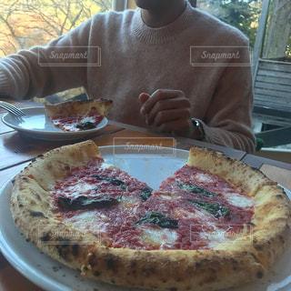 ピザのプレートをテーブルに座っている男の人の写真・画像素材[1653171]