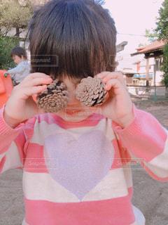 松ぼっくりを持っている女の子の写真・画像素材[1582271]